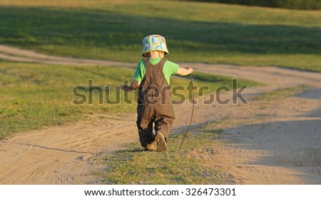Kid walking away on a country road - stock photo