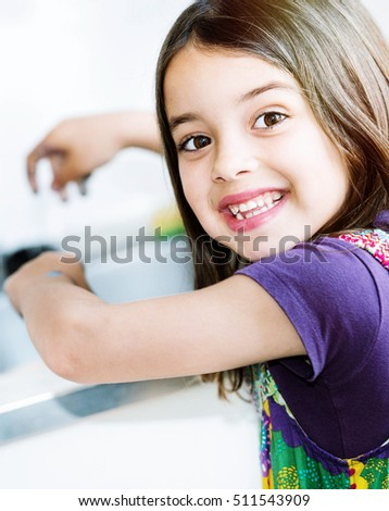 kid washing hands in the kitchen before eating