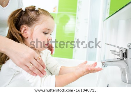 kid washing hands with adult - stock photo