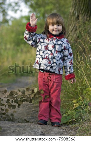 Kid waving for goodbye standing alone before long way in the trees - stock photo