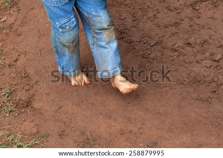 Kid wearing jeans trousers walking on muddy ground - stock photo