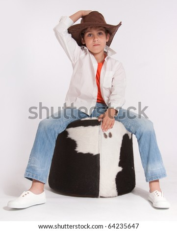Kid with a cowboy hat riding a cowhide footstool - stock photo