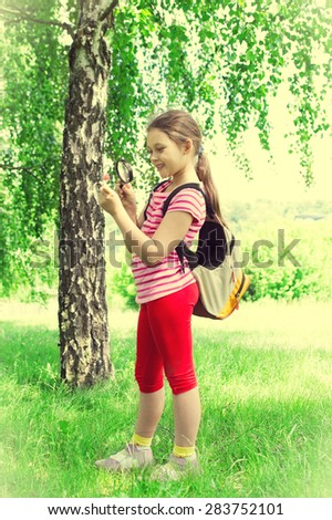 kid with a magnifying glass - stock photo
