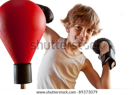 Kid with attitude during boxing training with punching ball.  Isolated against white. - stock photo
