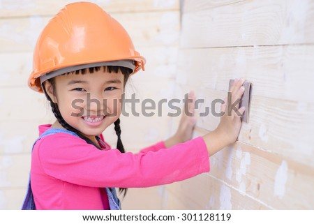 Kid with carpenter work sanding on wood and smile