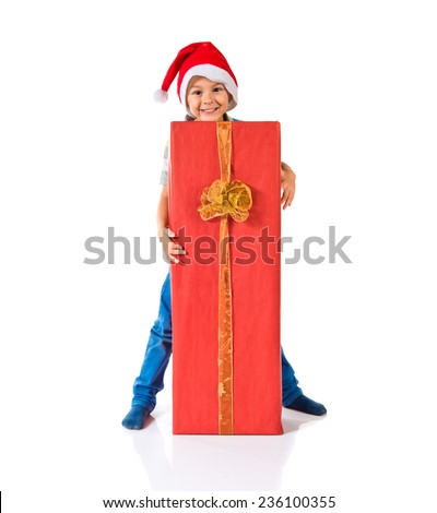 kid with christmas hat holding a big red gift - stock photo