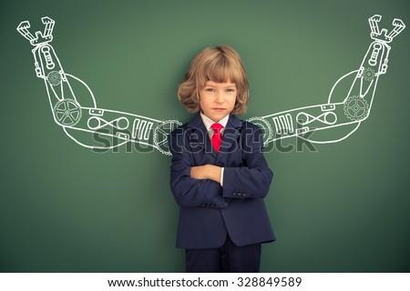 Kid with drawn robot hands against blackboard. Schoolchild in class - stock photo