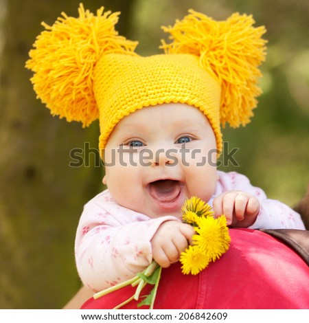 Kid with flowers. 3 month baby in yellow knitted cap with a bouquet of dandelions outdoor. Mother's Day, Father's Day concept. - stock photo