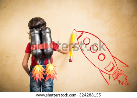 Kid with jet pack draw sketch on wall. Child playing at home. Success, leader and winner concept - stock photo