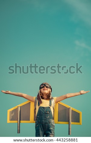 Kid with jet pack. Portrait of child against summer sky background. Kid pretend to be superhero. Child playing in summer outdoors. Success, leader and winner concept. Imagination and freedom concept - stock photo