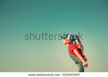 Kid with jetpack against autumn sky background. Child playing outdoors. Success, leader and winner concept. Retro toned - stock photo