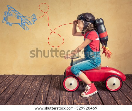 Kid with jetpack driving retro toy car. Child playing at home. Success, leader and winner concept - stock photo