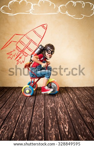 Kid with jetpack riding bike. Child playing at home. Success, leader and winner concept - stock photo