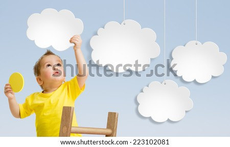 Kid with ladder attaching clouds to sky - stock photo