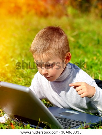 Kid with Laptop on the Grass in the Park - stock photo