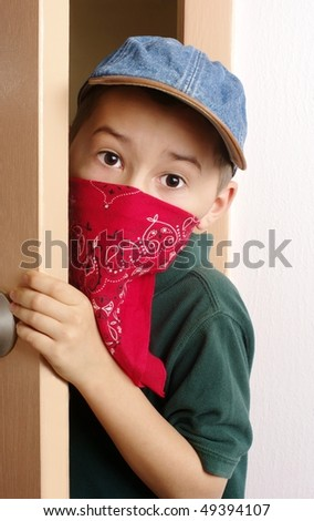 Kid with mask sneaking in through door - stock photo