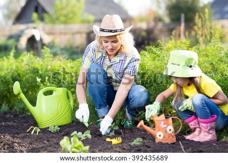 Kid with mother planting seedlings in garden - stock photo