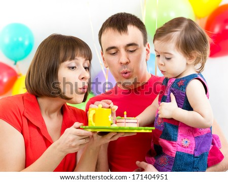 kid with parents celebrating birthday  and blowing candles on cake