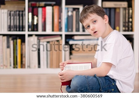 Kid with red book in the library. Looking at camera. He sits cross-legged on the floor. Dressed in a white t shirt and blue jeans - stock photo