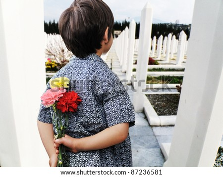 Kid with roses standing on the grave - stock photo