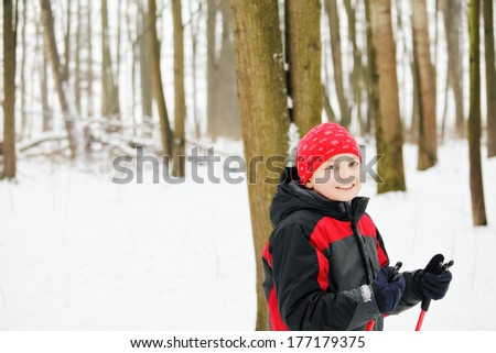 Kid with ski poles standing in winter forest photo with the space for copy - stock photo