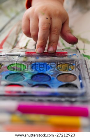Kid with some color paints - stock photo