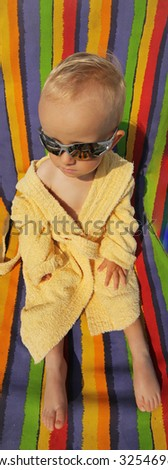 Kid with sunglasses on colorful sunbed - stock photo