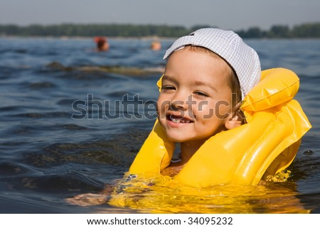 Kid with swimming vest in water - stock photo