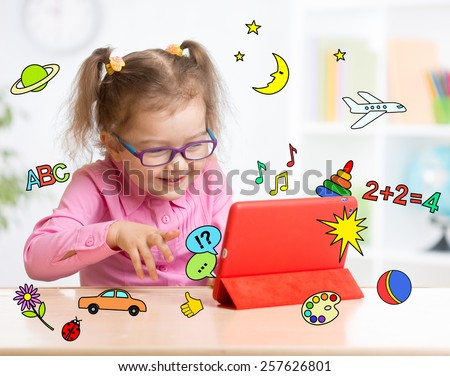 Kid with tablet computer in glasses. Early education. - stock photo