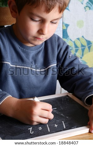 Kid writing on a blackboard - stock photo