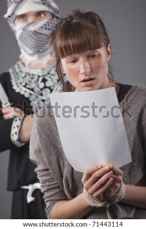 kidnapped and bounded woman reading terrorist demands - stock photo