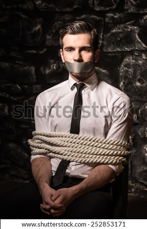 Kidnapped and tied up young man is sitting on the chair in dark room. - stock photo