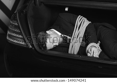 Kidnapped businessman. Black And White image of tied up young men lying in the car trunk - stock photo