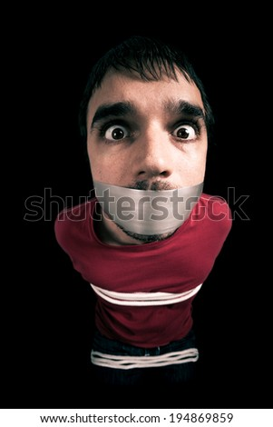 Kidnapped man hostage with tape over mouth and tied up with rope - stock photo