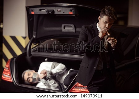 Kidnapped man. Tied up businessman lying in the car trunk and looking at camera while kidnapper smoking a cigar near him - stock photo