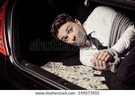 Kidnapped man. Tied up businessman lying in the car trunk full of paper currency and looking at camera - stock photo