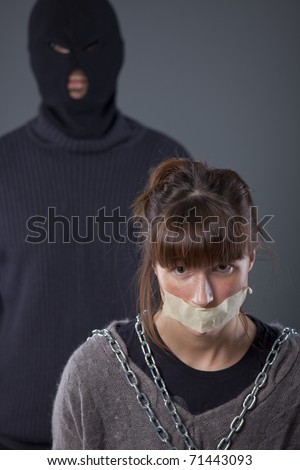 kidnapped, tied up female hostage and hijacker in balaclava - stock photo