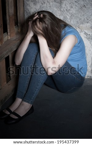 Kidnapped woman. Top view of young woman crying and holding hands in hair while sitting on the floor - stock photo