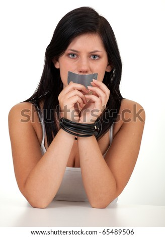 kidnapped young woman, hostage, tied hands by cable and gagged - stock photo