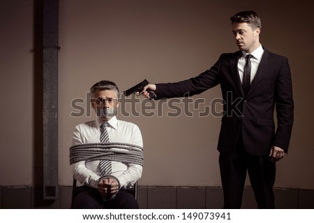 Kidnapper and victim. Tied up businessman sitting at the chair and looking at camera while young man in formalwear aiming him with gun - stock photo