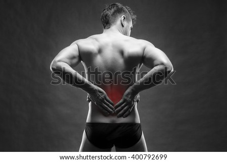 Kidney pain. Man with backache. Handsome muscular bodybuilder posing on gray background. Black and white photo with red dot - stock photo