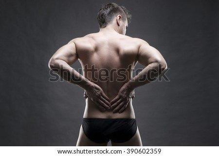 Kidney pain. Man with backache. Handsome muscular bodybuilder posing on gray background. Low key close up studio shot - stock photo