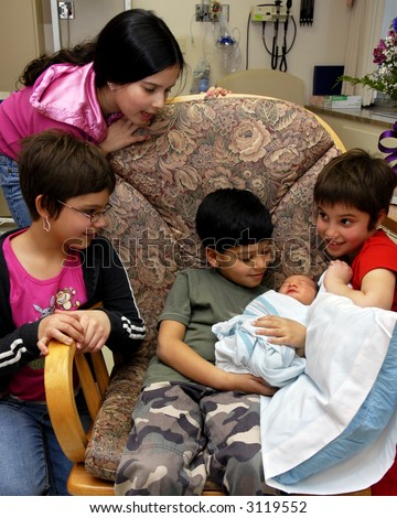 Kids admiring their newborn brother and cousin at the birthing center. - stock photo
