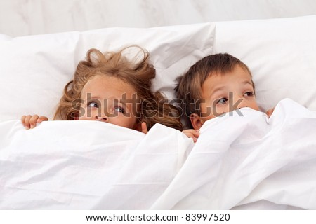 Kids afraid laying in bed and pulling the quilt on their heads - stock photo