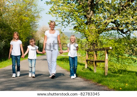 Kids and her mother walking down a path in spring, the mother is pregnant - stock photo