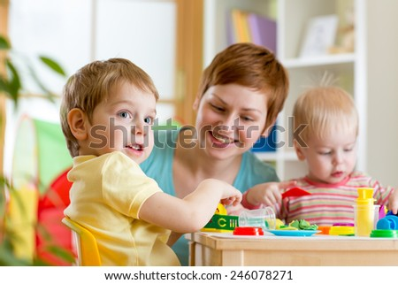 kids and mother play colorful clay toy - stock photo