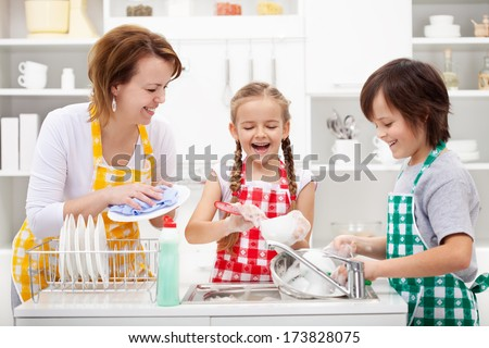 Kids and mother washing dishes - having fun together in the kitchen - stock photo