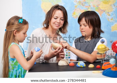 Kids and teacher in science class study the solar system - examining the planets from a scale model - stock photo