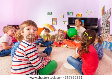 Kids and teacher sit in circle - stock photo