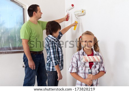Kids and their father painting a room using paint roller - focus on girl in foreground - stock photo